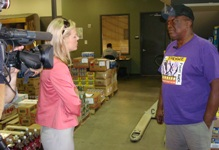 Liz Dannheim with CBS-42 talks to Otis Jackson, a volunteer with Bastrop County Food Pantry for a Food Drive story. Jackson said it costs $125 to fill the gas tank on their van, and that cuts into their food budget.