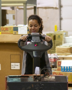 Community Events Coordinator, Molly Robbins learns how to operate a pallet jack.