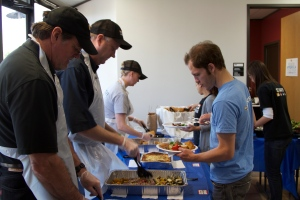 Left to Right: Charlie Ward, Chief Operating Officer; David Davenport, President & CEO; and Adrienne Longenecker, Chief Development Officer serve William Hubenschmidt,  AmeriCorps VISTA volunteer and fellow staff lunch.